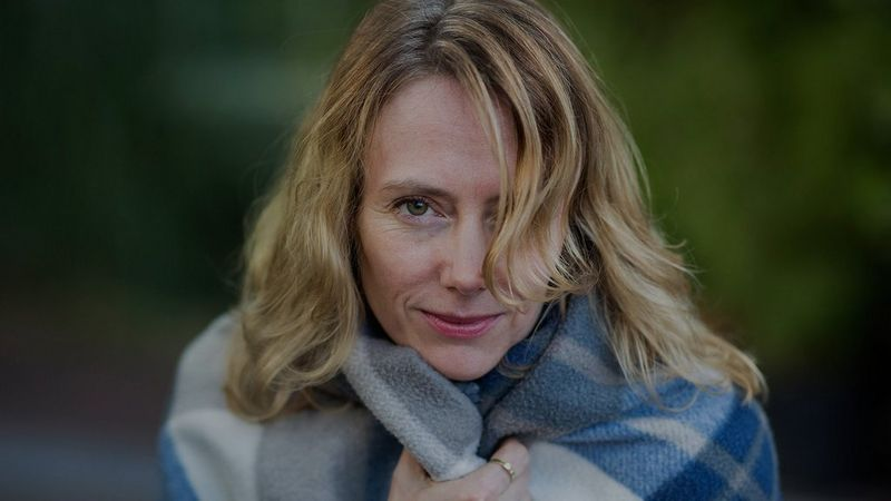 A portrait of a blonde woman outdoors, holding a soft blue checked fleece scarf close to her, taken with a Canon EF 85mm f/1.4L IS USM lens.